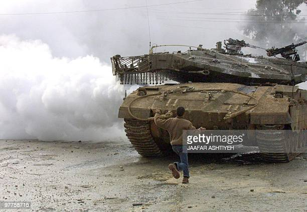 A young Palestinian throws stones at an Israeli tank in the Balata Palestinian refugee camp in the West Bank town of Nablus 10 January 2004...