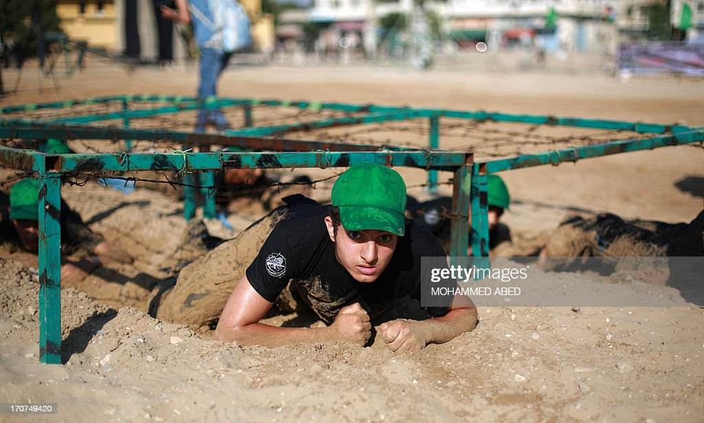 Young Palestinians crawl under barbed-wire during a summer physical training camp run by Hamas in Gaza City on June 17, 2013.