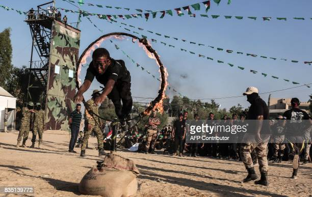 Young Palestinians jump though a ring of fire during a military graduation ceremony at a Hamas summer camp in Khan Yunis in the southern Gaza Strip...