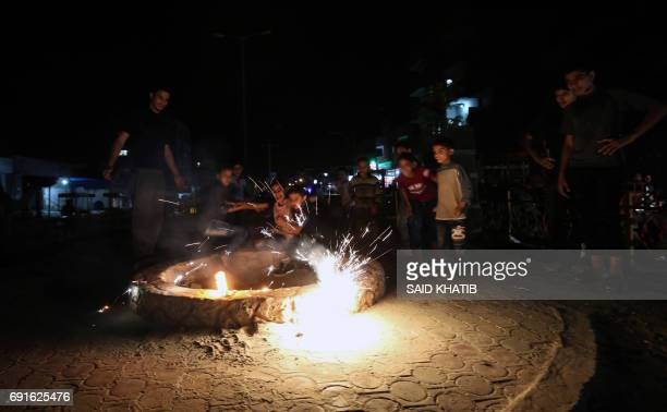 Young Palestinians play with fire crackers while celebrating the Muslim holy month of Ramadan at the town of Rafah in the southern Gaza Strip on June...