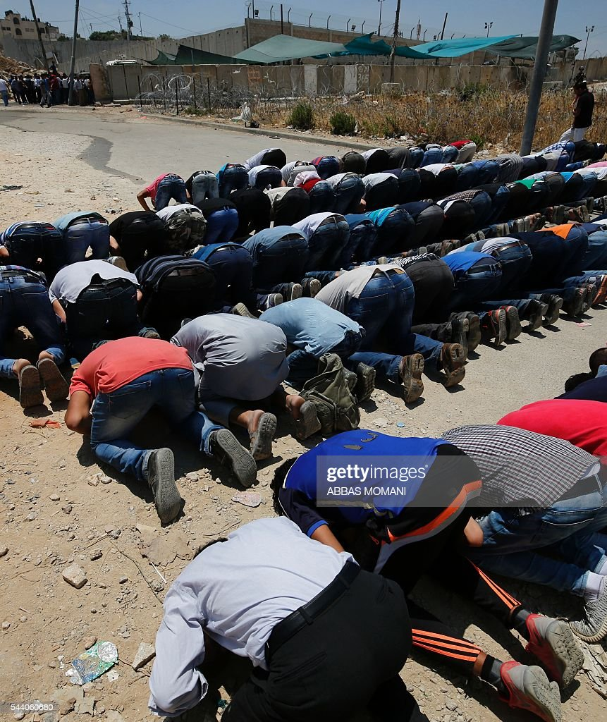 Young Palestinians pray near the Qalandia checkpoint between Ramallah and Jerusalem on July 1, 2016, after Israeli authorities banned men under 45 from accessing the Al-Aqsa mosque compound for Friday prayers. The Palestinian health ministry said that a middle-aged man had died from tear gas fired by Israeli forces during a clash at the Qalandia crossing. Israeli police said in a statement that three members of the security forces were injured by stones but it reported no Palestinian casualties. / AFP / ABBAS