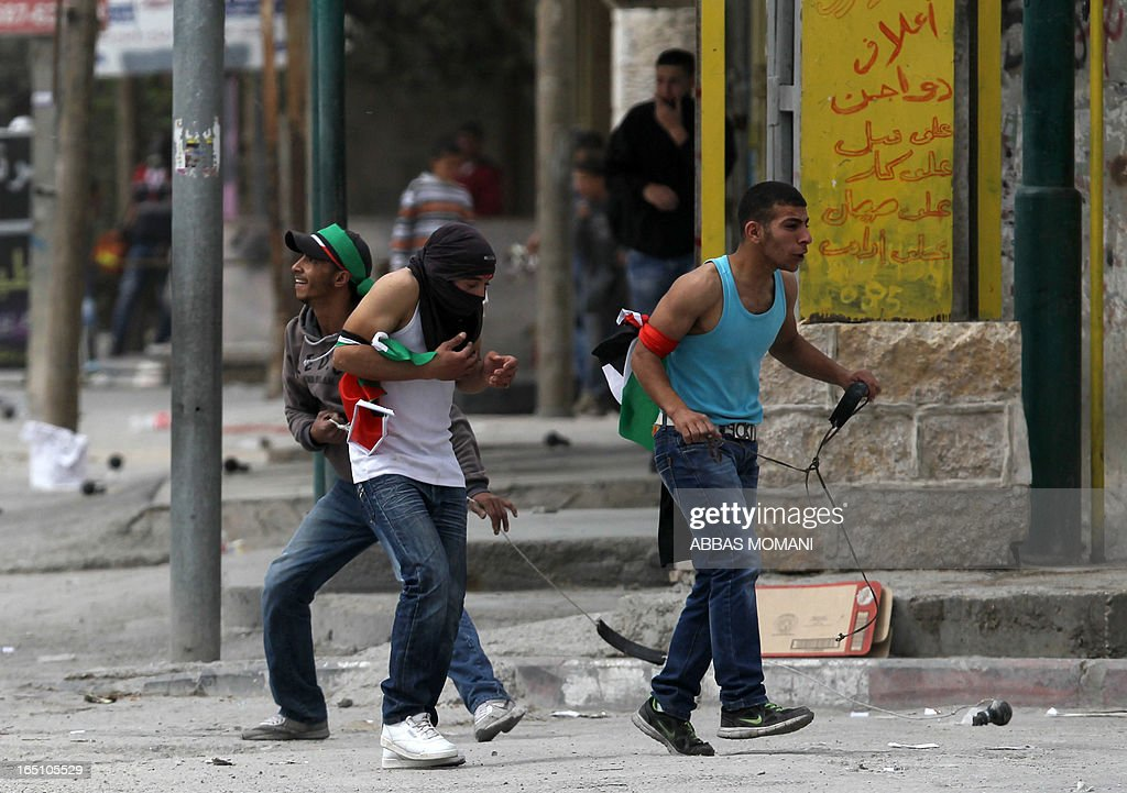 Young Palestinians step back after throwing stones towards Israeli soldiers during clashes following a rally commemorating the 37th anniversary of 'Land Day', on March 30, 2013 near the Qalandia checkpoint in the Israeli occupied West Bank. Nearly 200 Palestinians clashed with Israeli forces in Qalandia, who responded with tear gas.