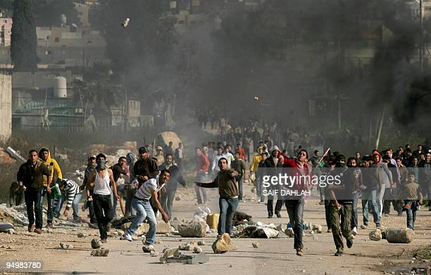 Young Palestinians throw stones at Israeli soldiers during clashes in the village of Baqa alSharqiyah near the West Bank city of Tulkarem on January...