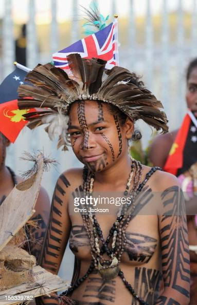A young Papua dancer looks on as Prince Charles Prince of Wales and Camilla Duchess of Cornwall arrive into Jackson's International Airport on...