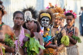 Young Papua dancers look on as Prince Charles Prince of Wales and Camilla Duchess of Cornwall arrive into Jackson's International Airport on November...