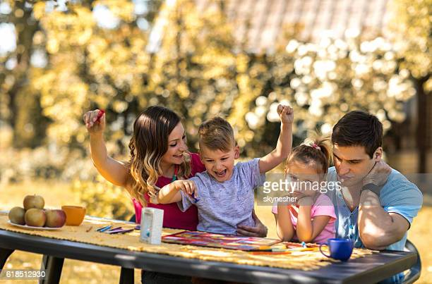 Young parents and children playing board game in the backyard.