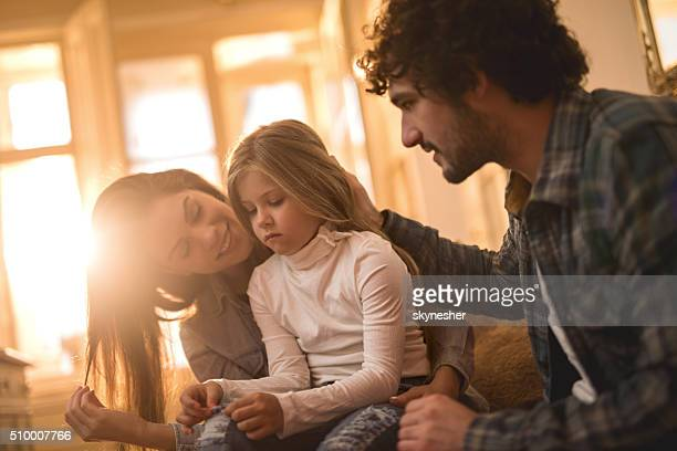 Young parents consoling their sad daughter at home.