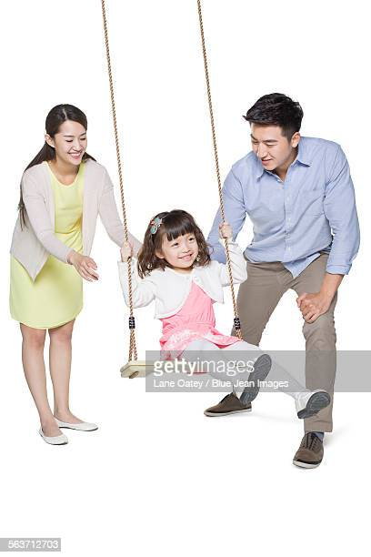 Young parents pushing daughter on swing