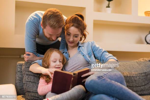 Young parents reading interesting book to daughter at home