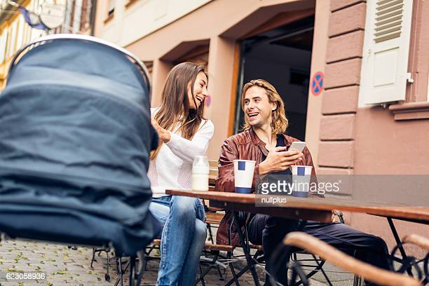 Young parents with baby stroller having coffee at a cafe