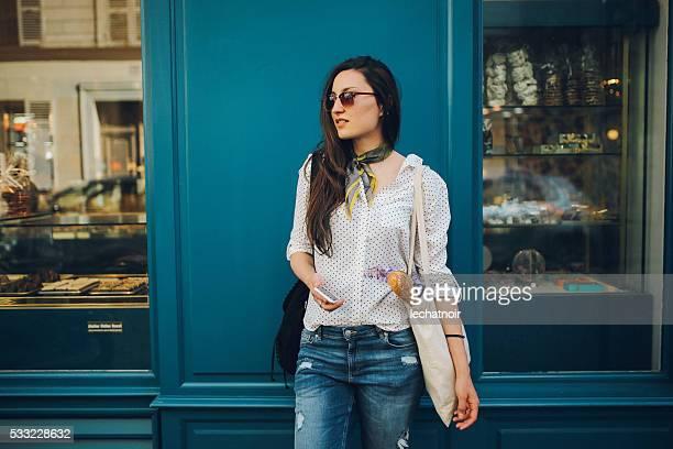 Joven mujer comprando parisino en una panadería