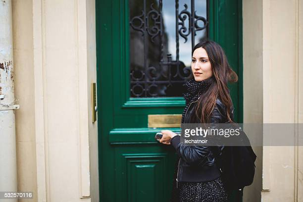 Young Parisian woman in font of her apartment
