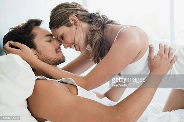 Young partially nude couple embracing in bed