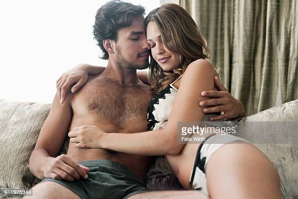 Young partially nude couple sitting on sofa