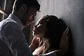 young passionate couple able to kiss while standing near the wall