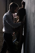 young passionate couple in sexual scene standing near the wall