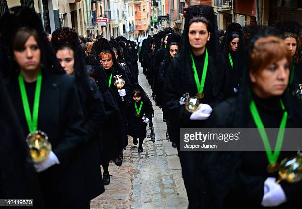 A young penitent walks with others up Calle Balborraz during the Holy Week procession of the Cofradia de la Virgen de la Esperanza on April 5 2012 in...