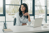 young pensive african american businesswoman sitting at workplace