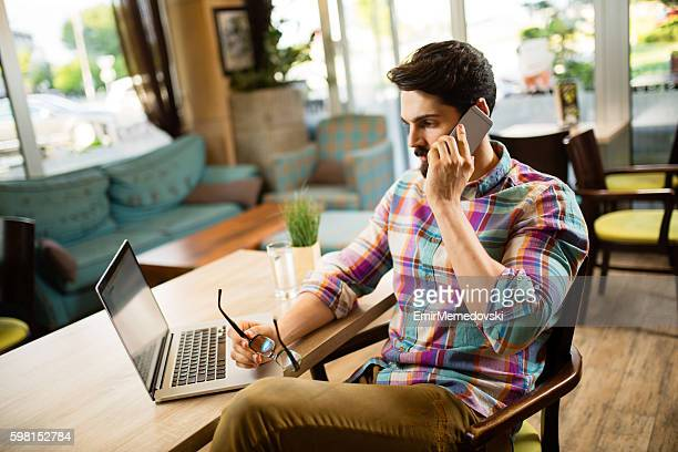Young pensive businessman is talking on his mobile phone.