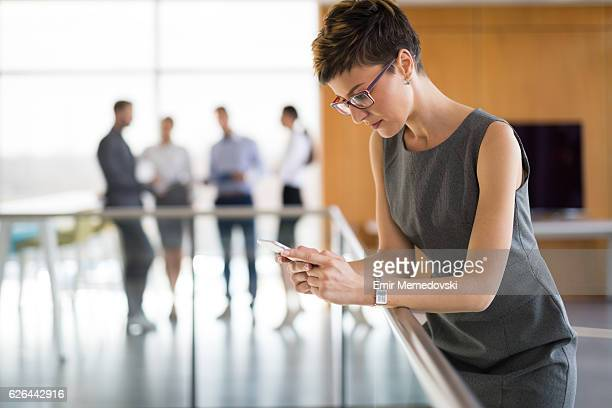 Young pensive businesswoman typing text message