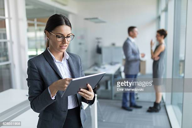 Young pensive  businesswoman using digital tablet in the office