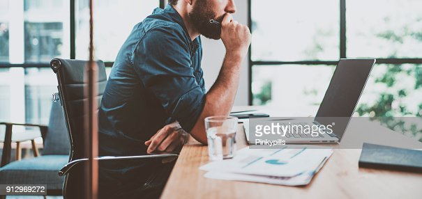 Young pensive coworker working at sunny work place loft while sitting at the wooden table.Man analyze document on laptop display.Blurred background.Horizontal wide. : Stock Photo