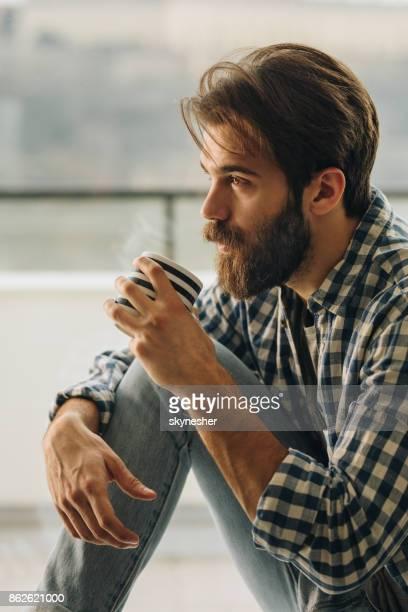 Jeune songeur homme jouir dans la tasse de café par la fenêtre.