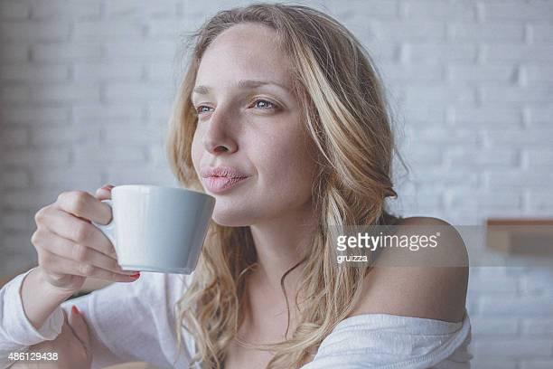 Songeur jeune femme au café profitant tasse de café