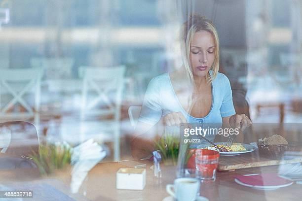 Joven mujer pensativa en el restaurante mientras disfruta de un delicioso plato