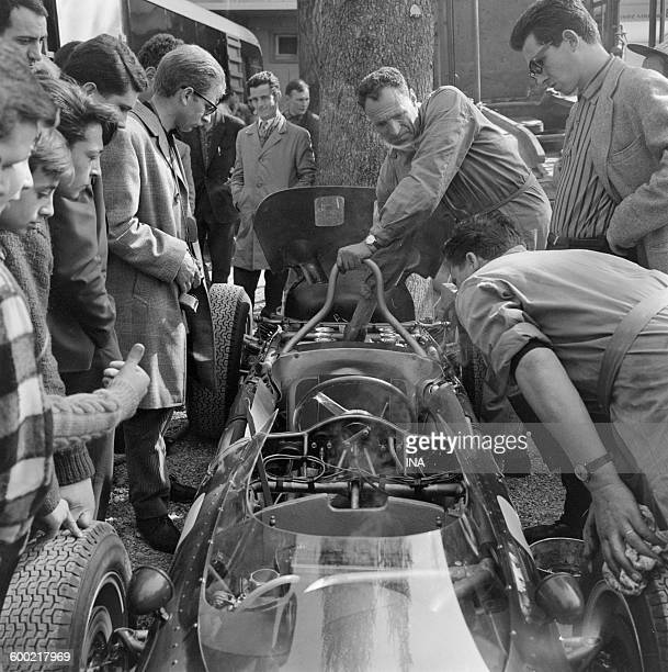 Young people and mechanics tilted on a racing car during Grand Prix of Pau