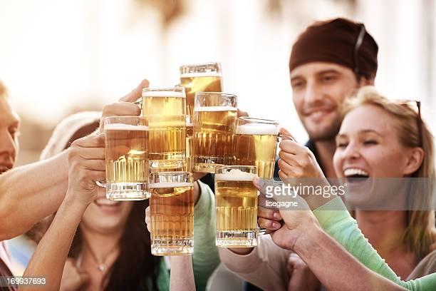 Los jóvenes en bistro con cerveza