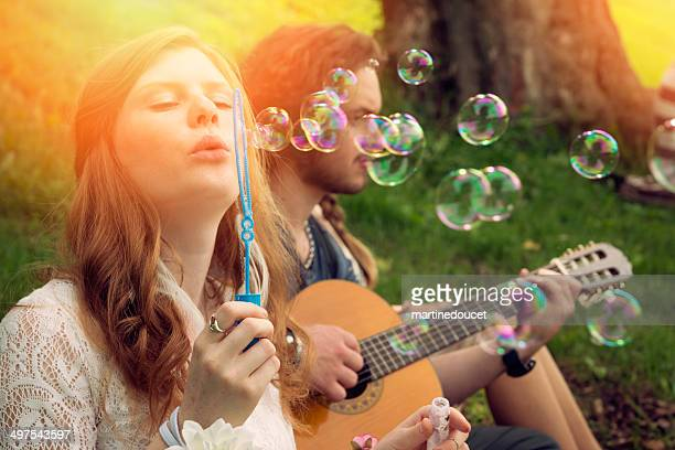 Young people blowing bubbles and playing guitar in park.
