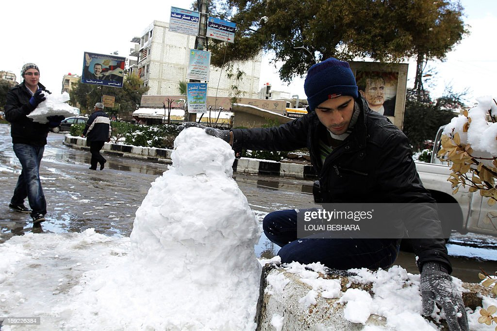 Young people build a snowman on January 10, 2013 in the Syrian capital of Damascus after heavy snow falls. Snow carpeted Syria's war-torn cities but sparked no let-up in the fighting, instead heaping fresh misery on a civilian population already enduring a chronic shortage of heating fuel and daily power cuts. AFP PHOTO / LOUAI BESHARA