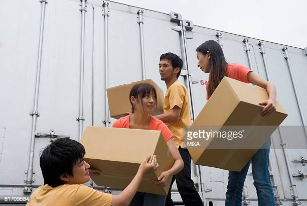 Young people carrying boxes