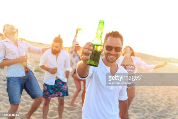 Junge Menschen jubeln am Strand