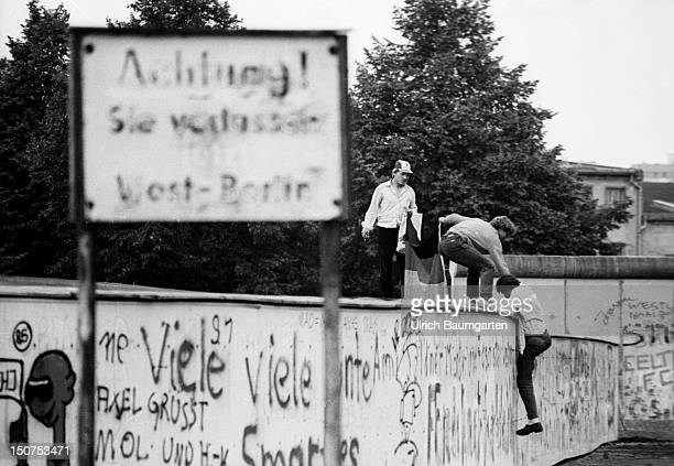 BERLIN AUGUST 89 Young people clamb up the Berlin wall beside a sign with the writing Attention you just leave West Berlin