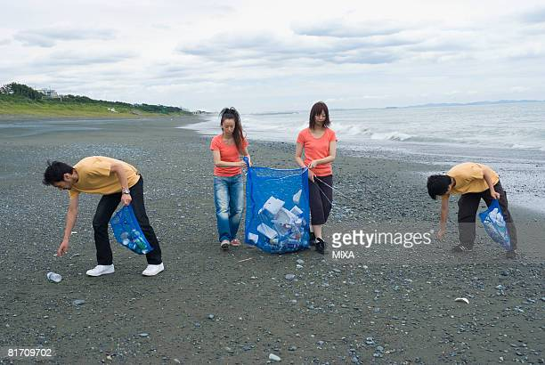 Young people cleaning beach