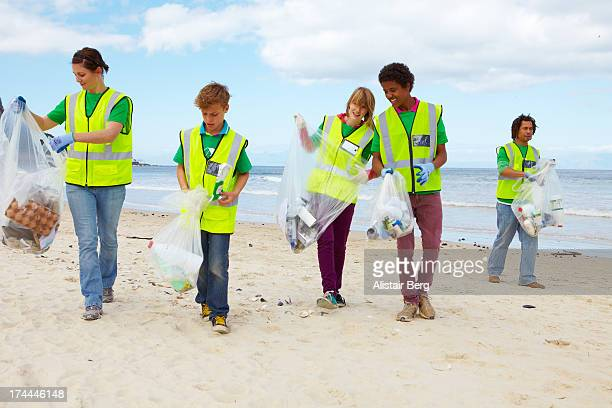 Young people cleaning up a beach