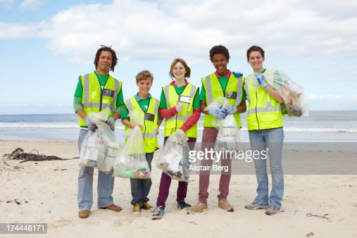Young people cleaning up rubbish on a beach : Stock Photo