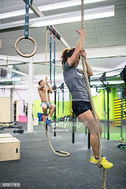 Junge Menschen Klettern Seil im Fitness-Center