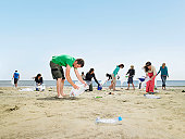 Young people collecting garbage on beach