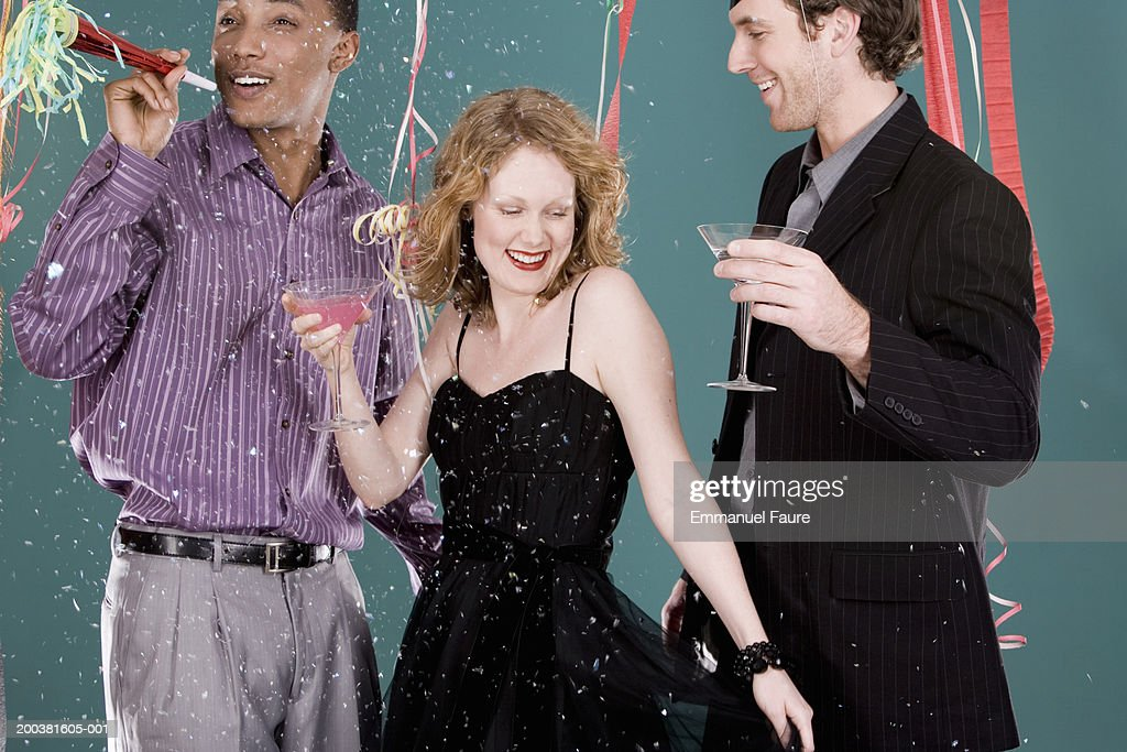 Young people dancing and holding noisemaker at party : Stock Photo