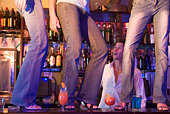 Young people dancing on a bar counter with bartender looking on