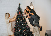 Young people decorate fir-tree for holidays of Christmas and New Year at home