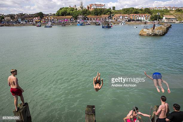 Young people dive jumping off Folkestone Harbour into the sea water after the annual Trawler race and fun day in Folkestone Kent England United...