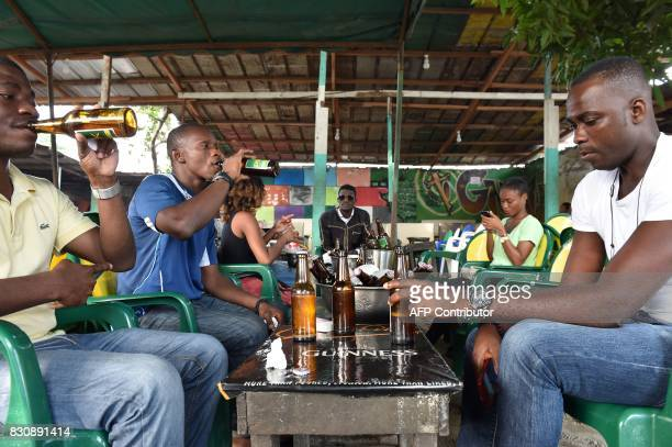 Young people drink beer at a bar in Abidjan on July 13 2017 On posters and huge billboards around the country rival ads by two breweries often side...