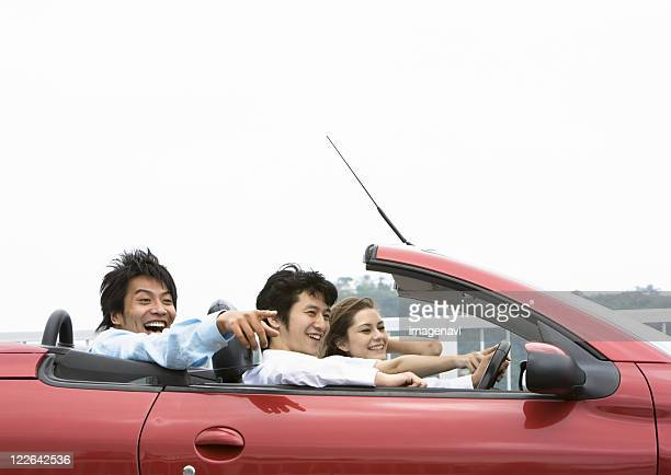 Young people driving a convertible