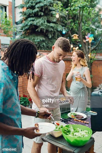 Os jovens de comer no Churrasco festa.