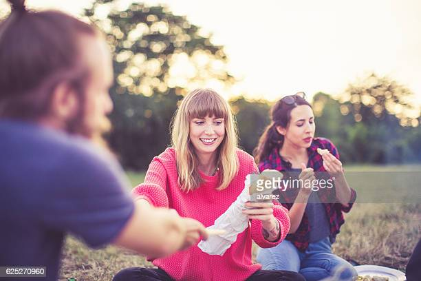 Young people eating food in the park
