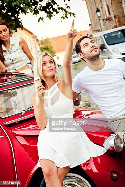 Young people eating ice cream by car
